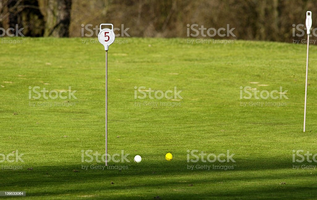 two golf balls on the putting green