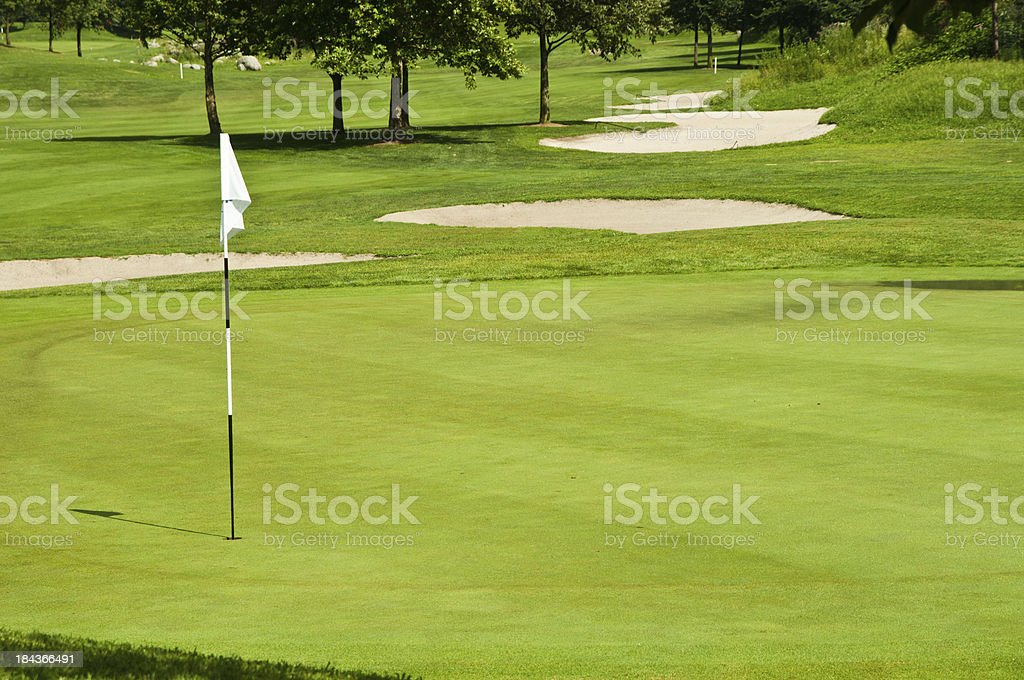 putting green with flag on a golf course in Switzerland royalty-free stock photo