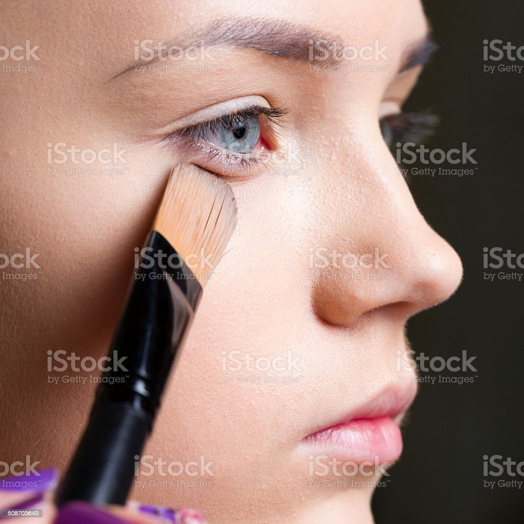 Putting Make up on face of young woman stock photo