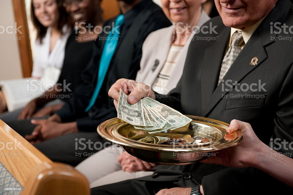 Putting Money in a Collection Plate stock photo