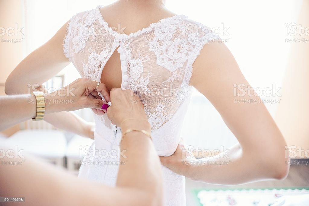 Putting on wedding dress stock photo
