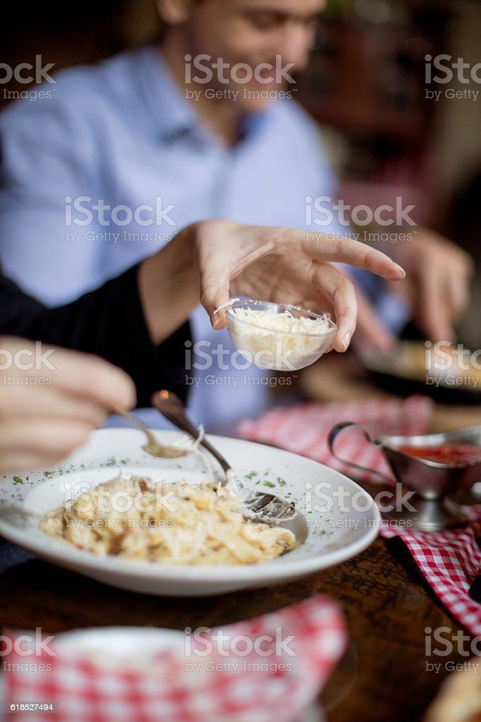 Putting parmesan cheese on pasta stock photo