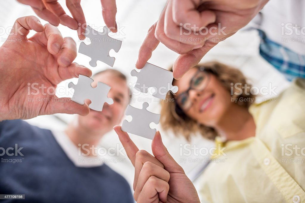 Putting pieces of a puzzle together stock photo