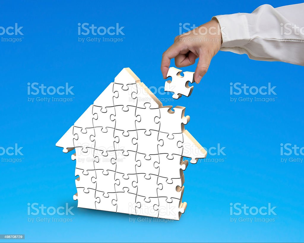 Putting puzzle in house shape stock photo