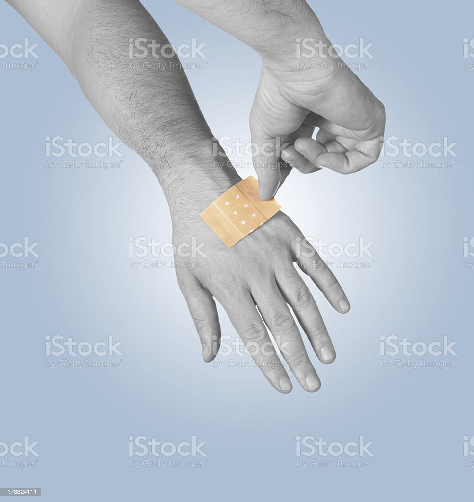 Putting small adhesive, bandage stock photo