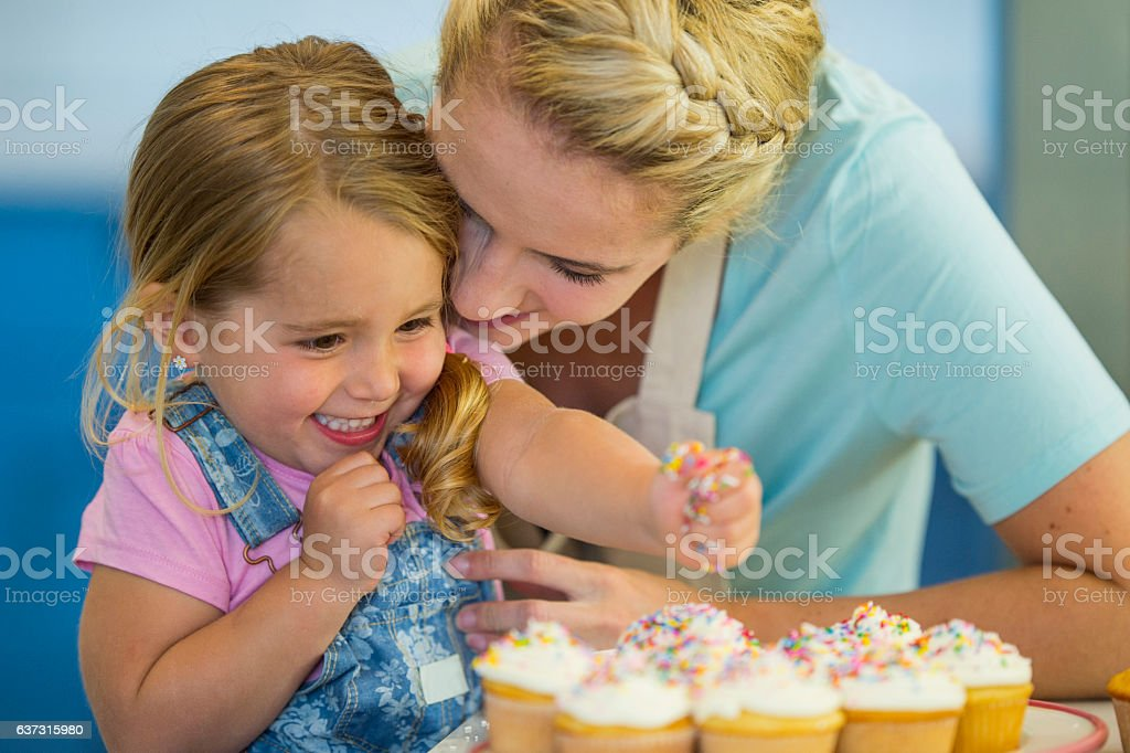 Putting Sprinkles on Cupcakes stock photo