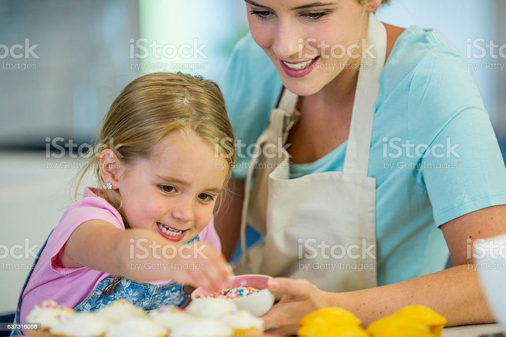 Putting Sprinkles on Cupcakes stock photo