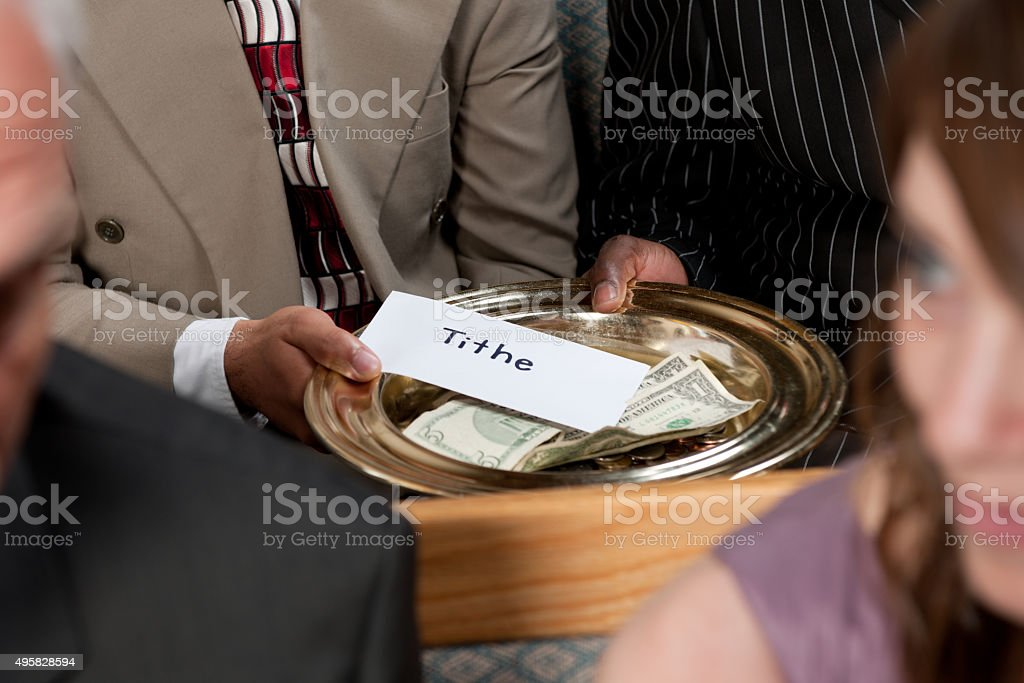 Putting Tithe in the Offering Plate stock photo