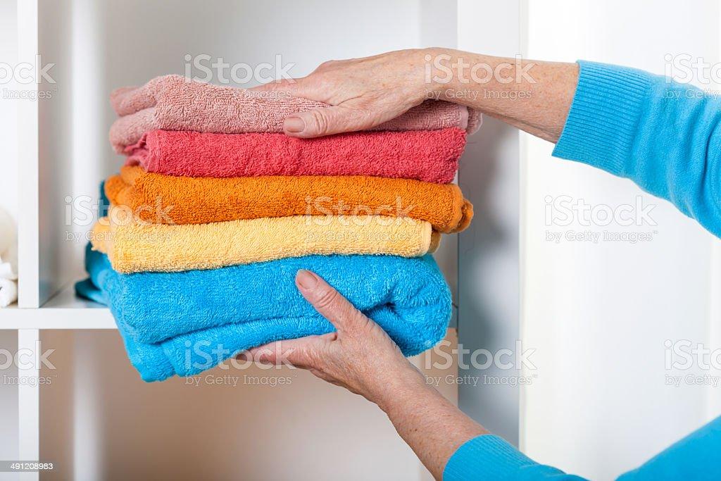 Putting towels on shelf stock photo