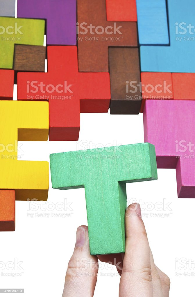 putting T-shaped block in multicoloured puzzle stock photo