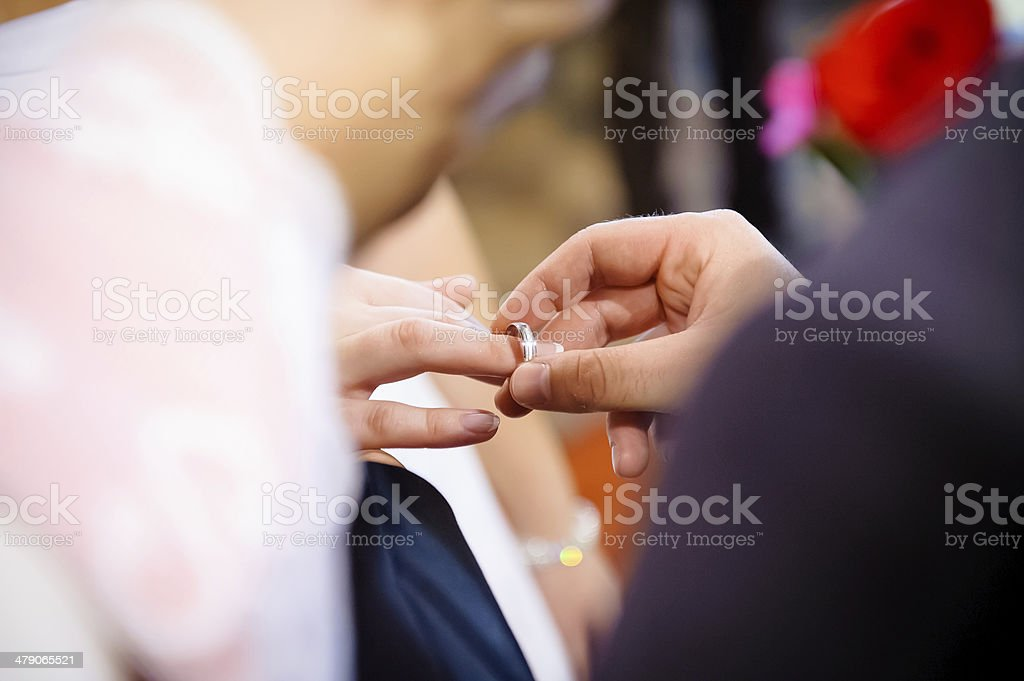 Putting wedding ring on bride's finger. stock photo