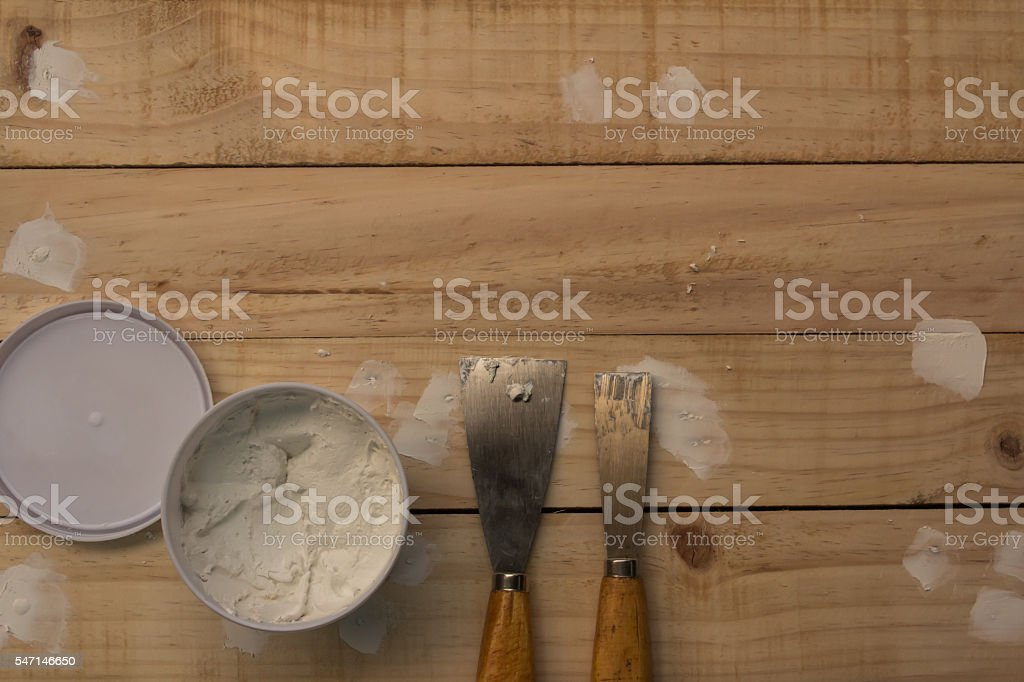 Putty knife and the wooden floor. stock photo