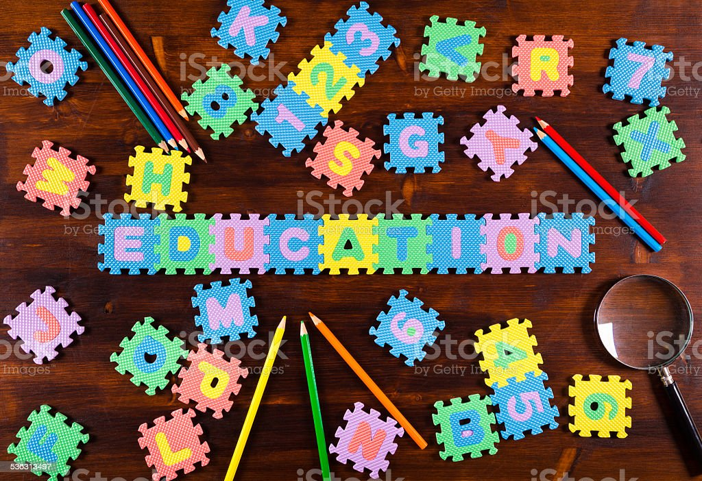 puzzle letters with pencils on wooden background stock photo