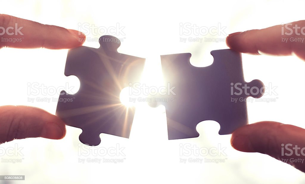 Puzzle pieces and human hands stock photo