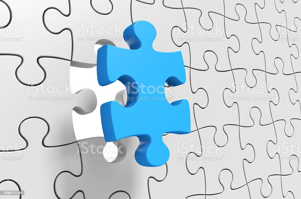 Puzzle solution, final jigsaw piece being inserted for completion stock photo