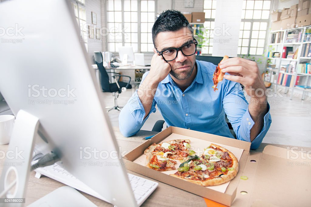 Puzzled businessman try to eating pizza at the office stock photo