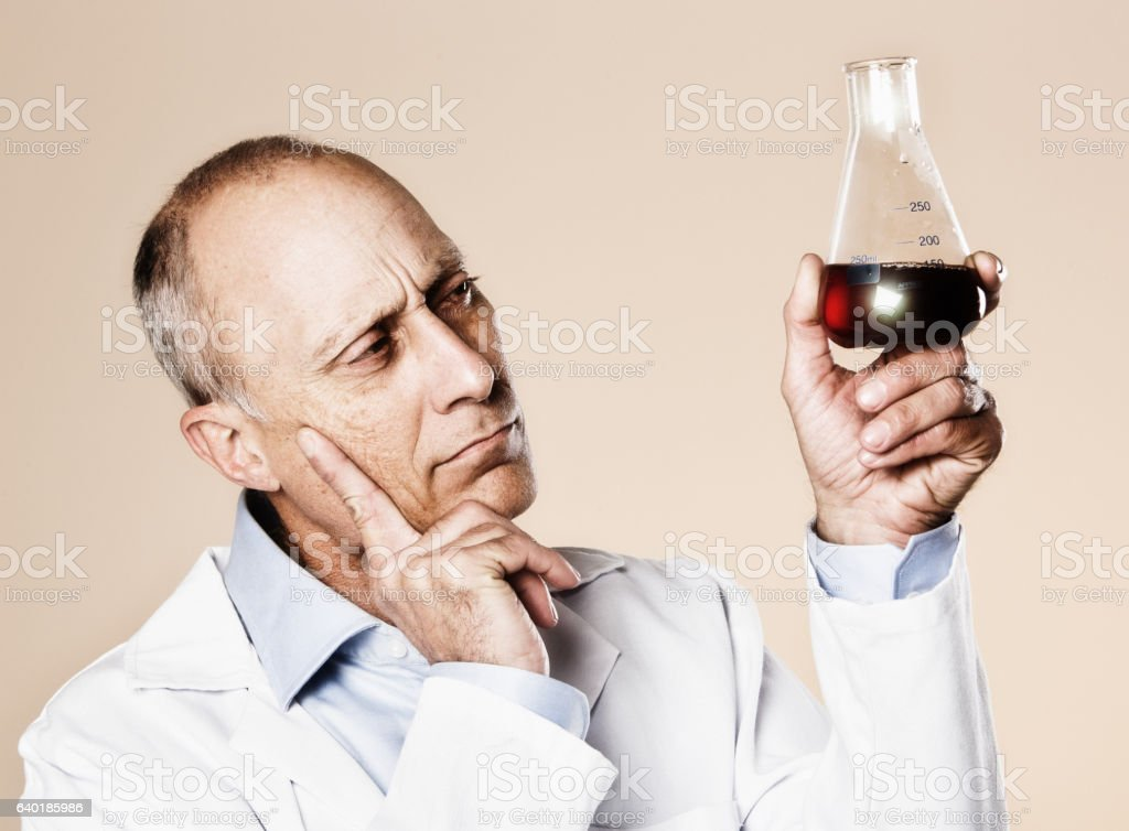 Puzzled scientist frowns, considering dark-red fluid in laboratory flask stock photo