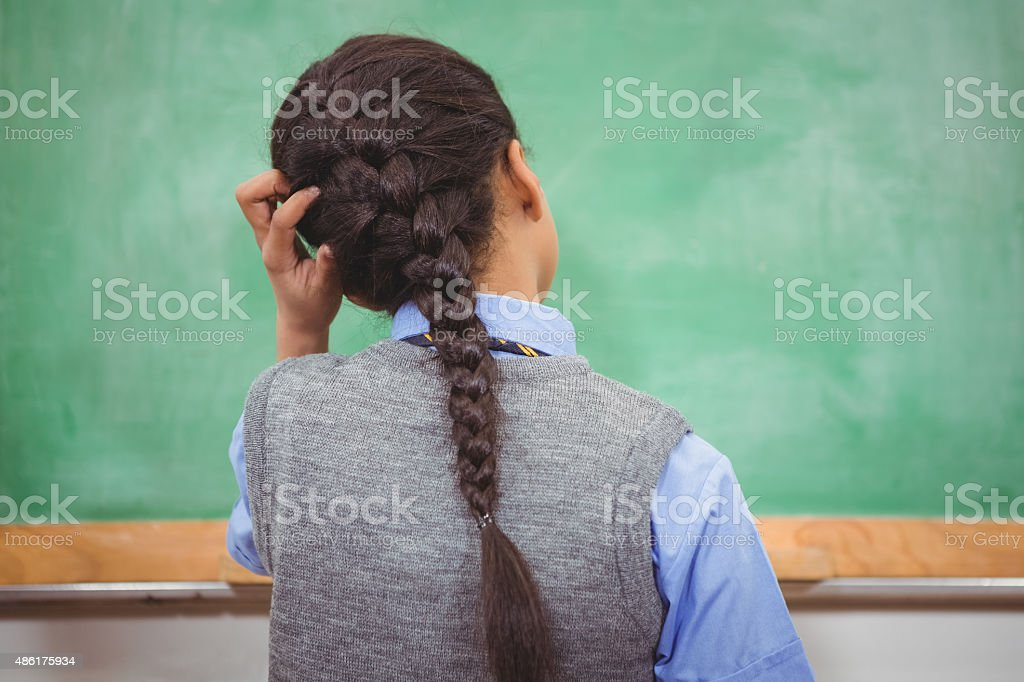 Puzzled student scratching their head stock photo