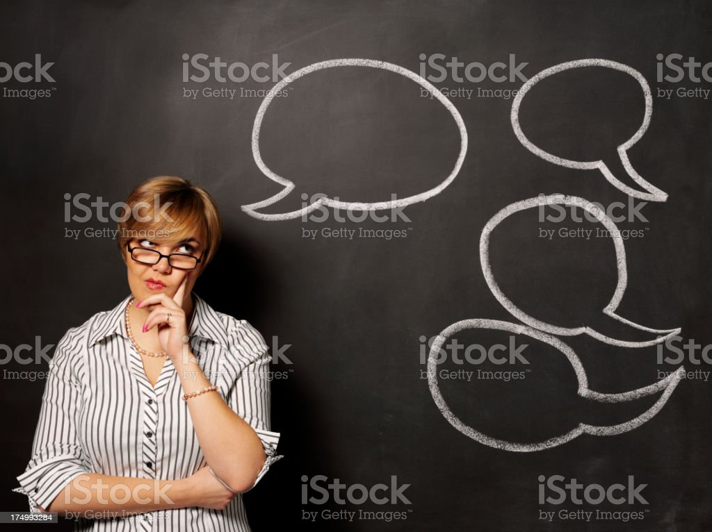 Puzzled Women with Speech Bubbles on a Blackboard royalty-free stock photo