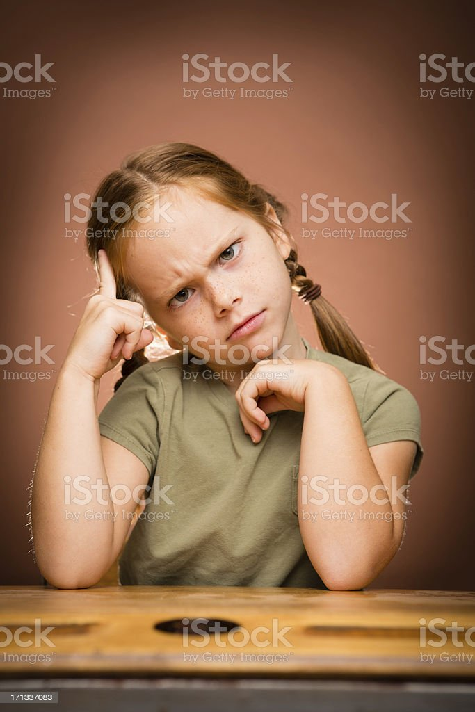 Puzzled Young Girl Student Sitting at School Desk royalty-free stock photo