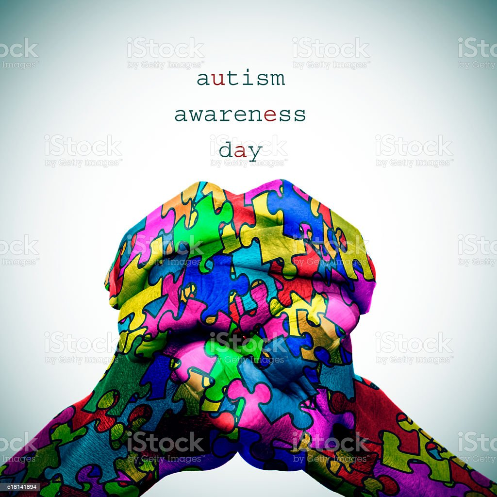 puzzle-patterned hands and text autism awareness day stock photo