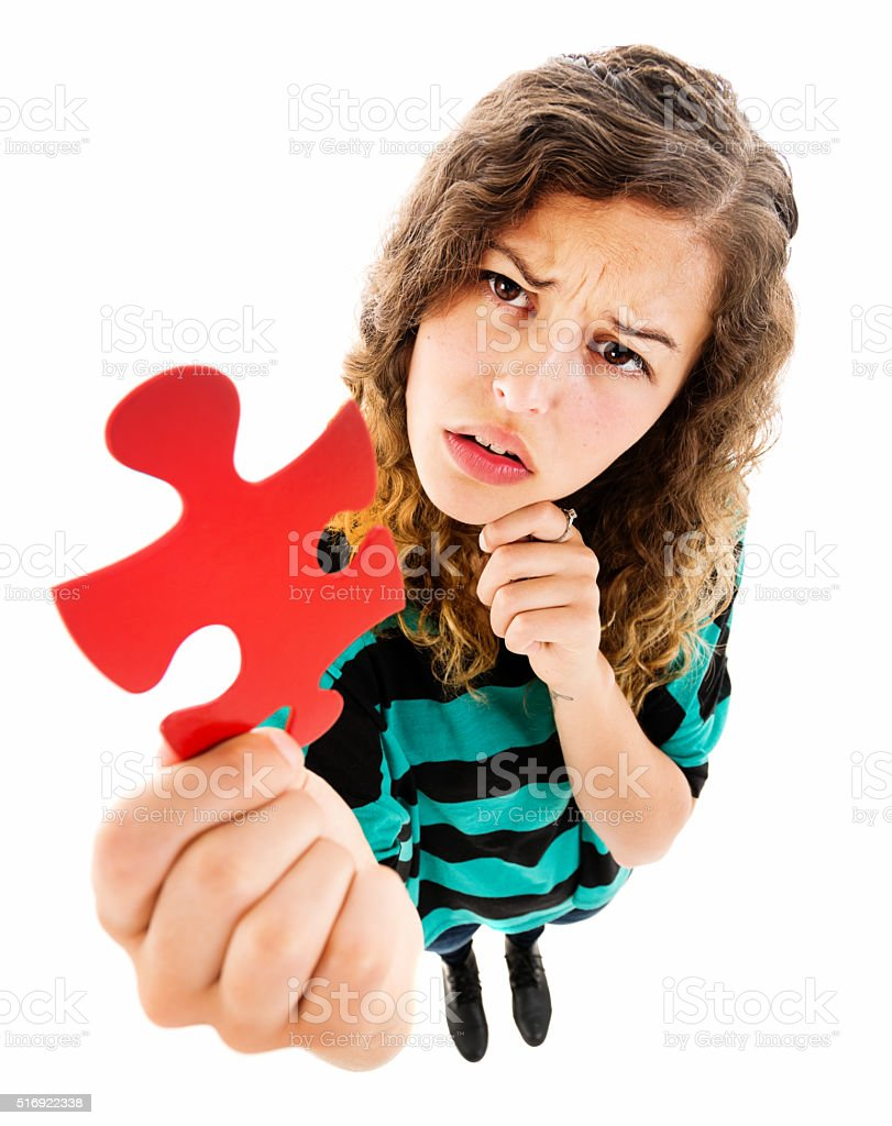 Puzzling over a puzzle: pretty girl with jigsaw piece stock photo