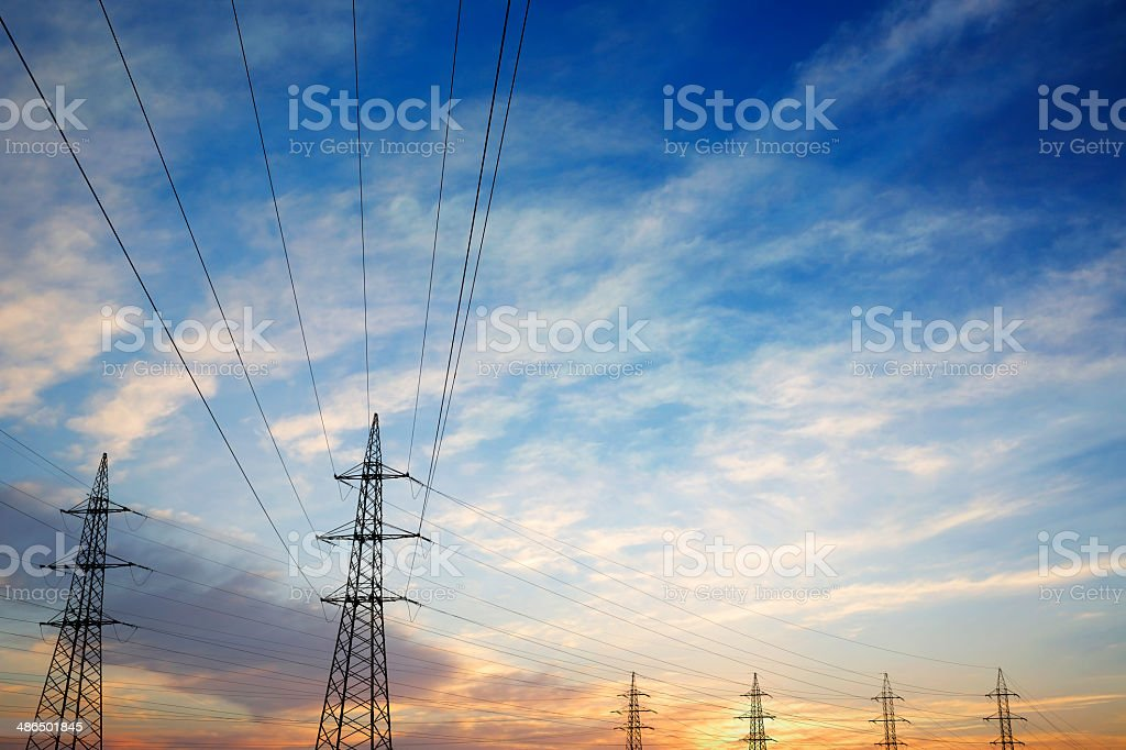 Pylons and power lines at sunset with vibrant sky stock photo
