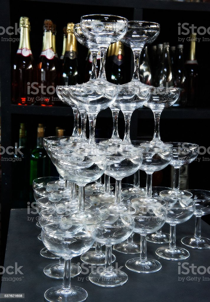 Pyramid of champagne glasses with bottles stock photo