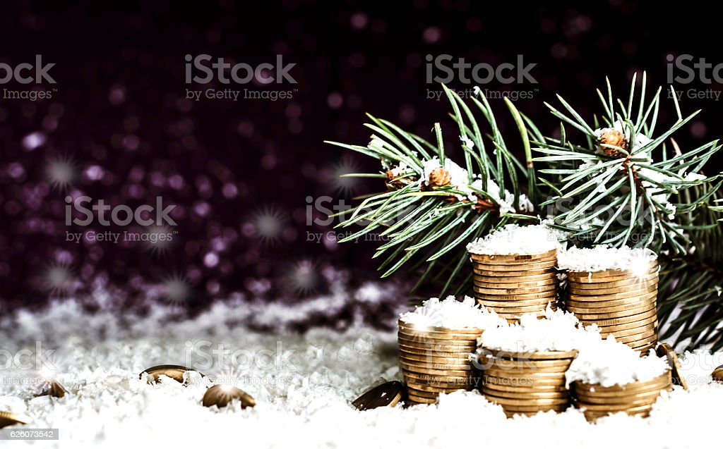 Pyramid of coins and the coins scattered over in the snow stock photo