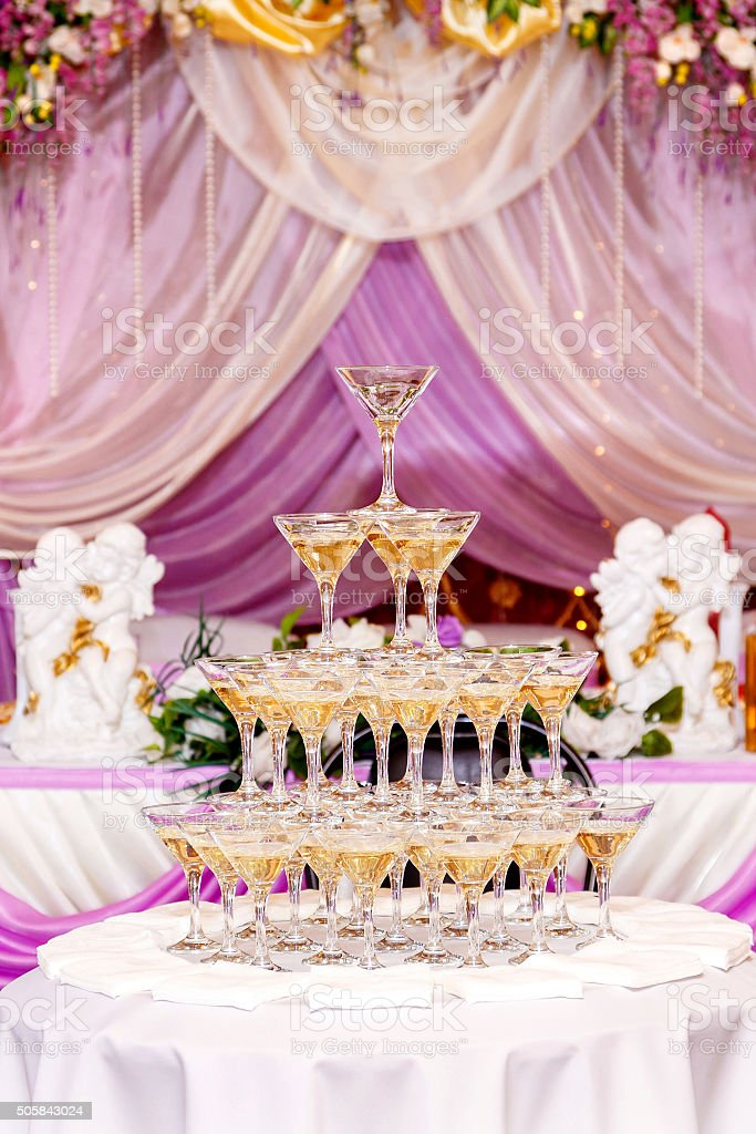 Pyramid of glasses with champagne in purple wedding interior. stock photo
