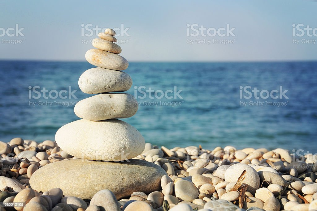 Pyramid of stones for meditation lying on sea coast stock photo