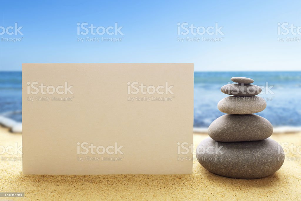 Pyramid of the stones with blank paper on sandy beach royalty-free stock photo