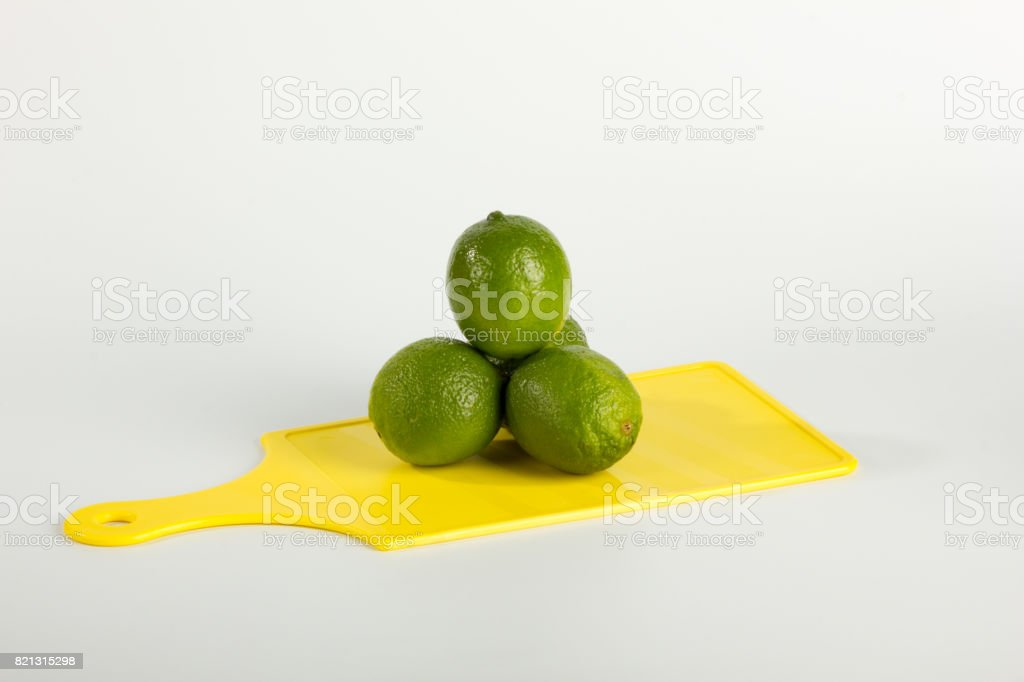Pyramidal Limes Stacked on Yellow Cutting Board stock photo