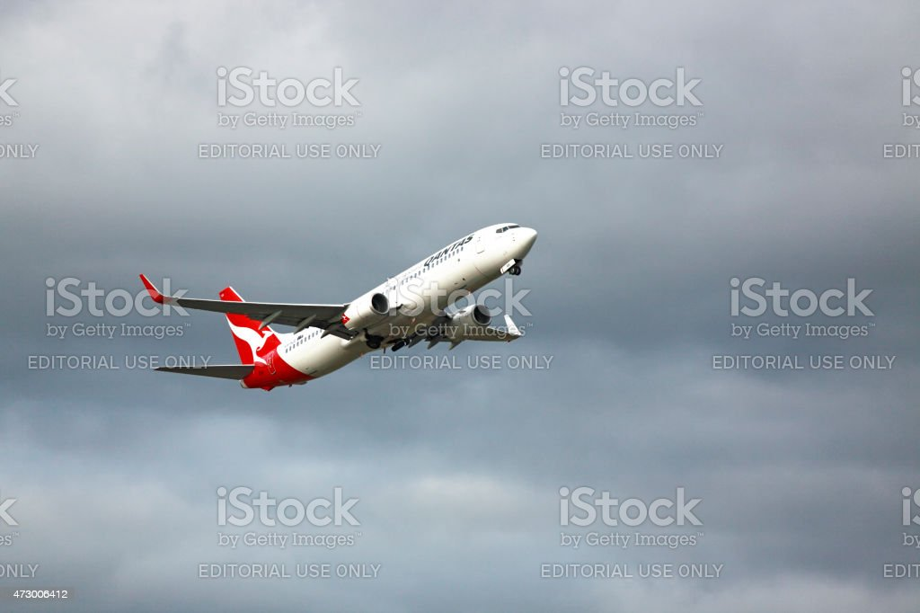 Qantas plane taking-off with dark moody sky stock photo