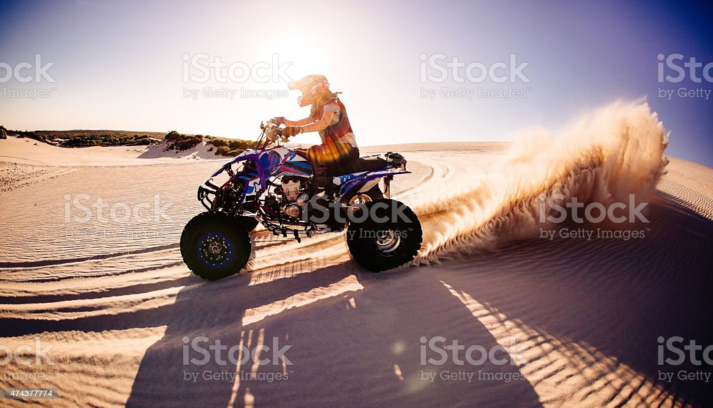 Quad biker kicking up sand while racing on sand dunes stock photo