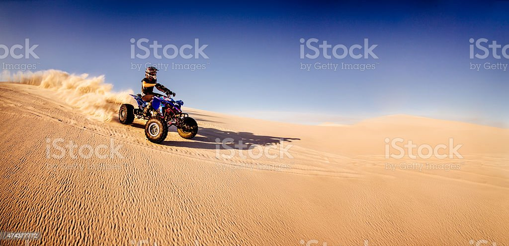 Quad biker racing downhill in a desert race stock photo