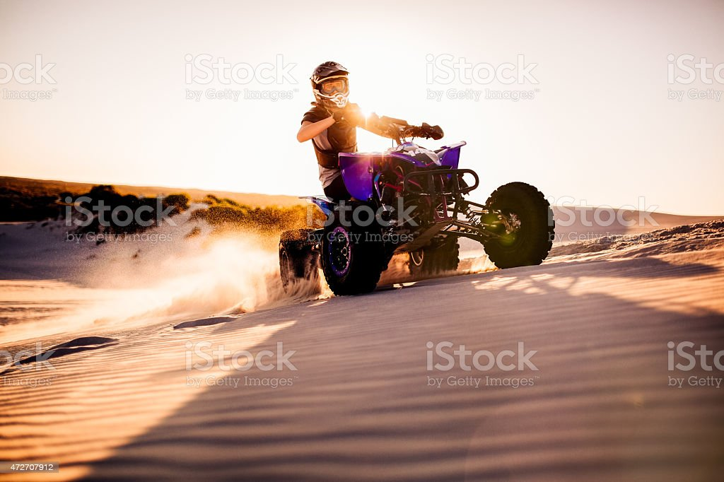 Quad racer driving up a sand dune with sun flare stock photo