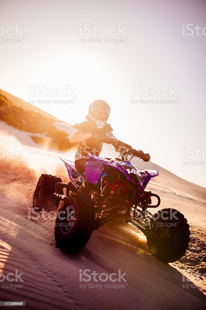 Quad racer maneuvering over sand tracks with sun flare behind stock photo
