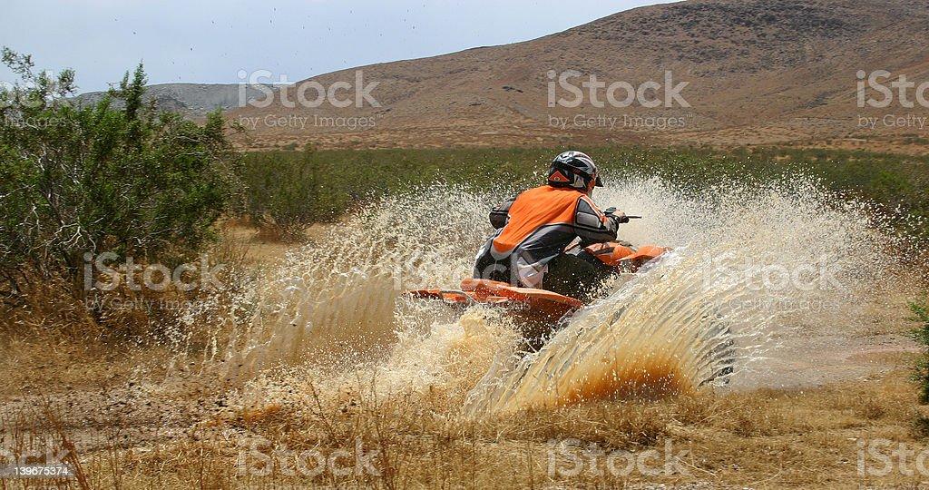 Quad Rider going through Mud Puddle stock photo