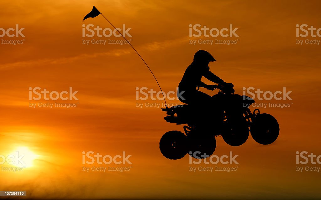 Quadbike jumping at sunset royalty-free stock photo