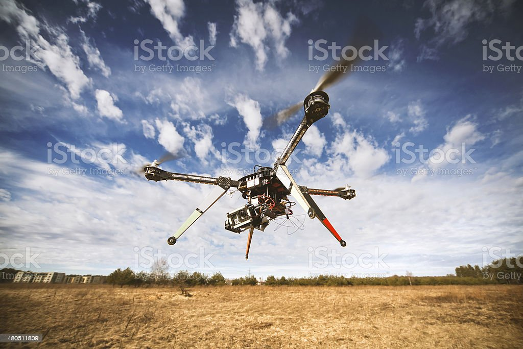 Quadrocopter drone flying in the sky stock photo
