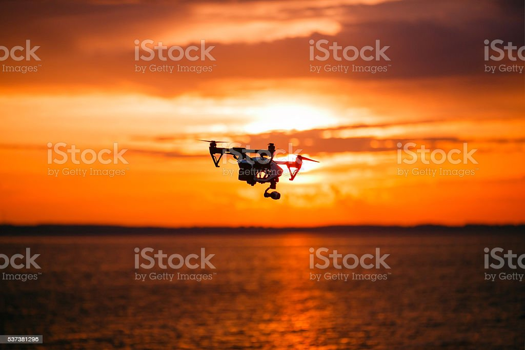 quadrocopter drone with remote control. Dark silhouette against colorfull sunset stock photo
