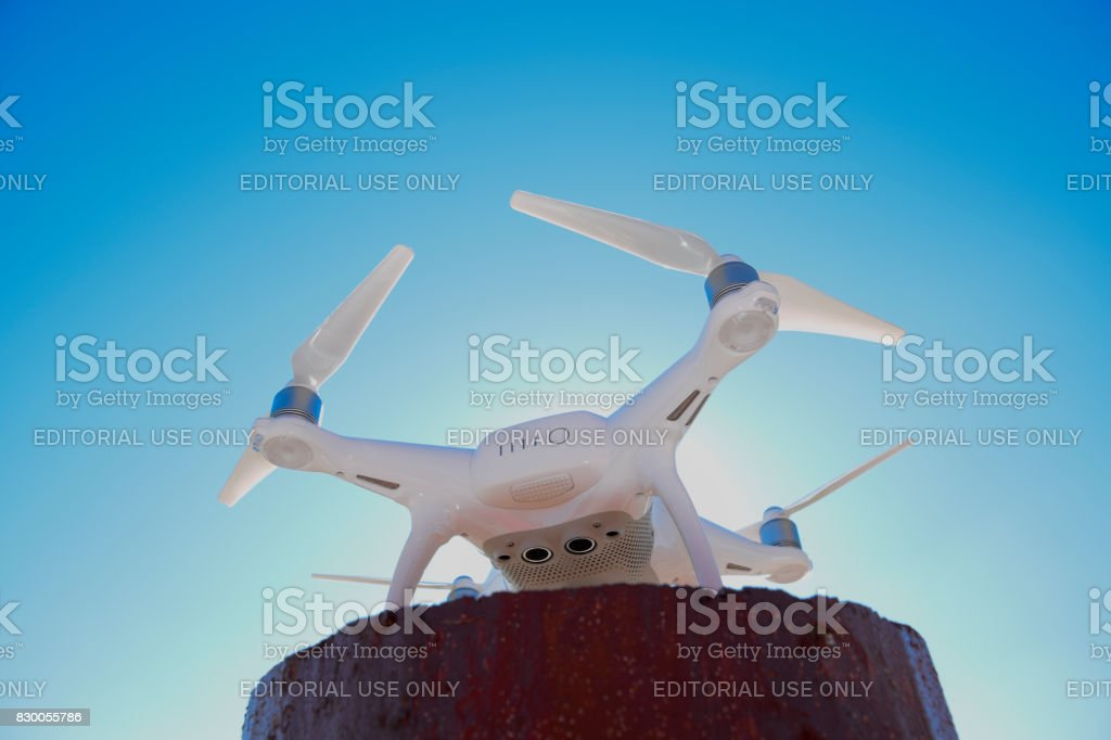 Quadrocopter Phantom 4 against the blue sky in the sun. Backlight. Dron is an innovative flying robot. stock photo