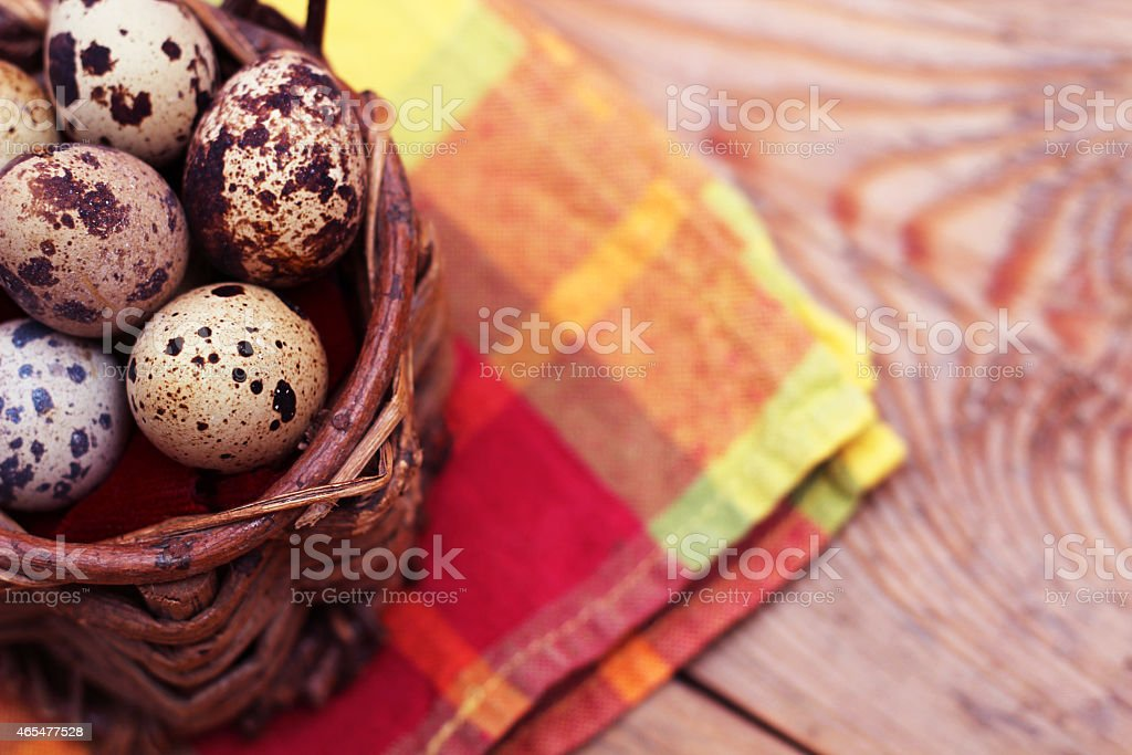 Quail eggs in a wicker basket on a wooden background stock photo