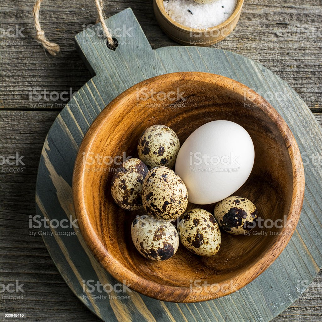 Quail eggs in a wooden bowl on  cutting board   dark stock photo