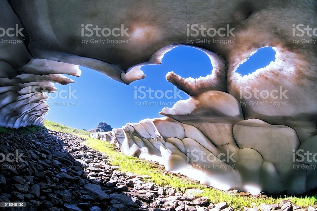 Quaint intricate mountain snow cave from inside scenery stock photo