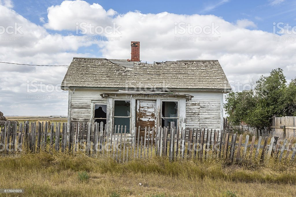 quaint little old abandoned house sitting behind broken wood fence stock photo