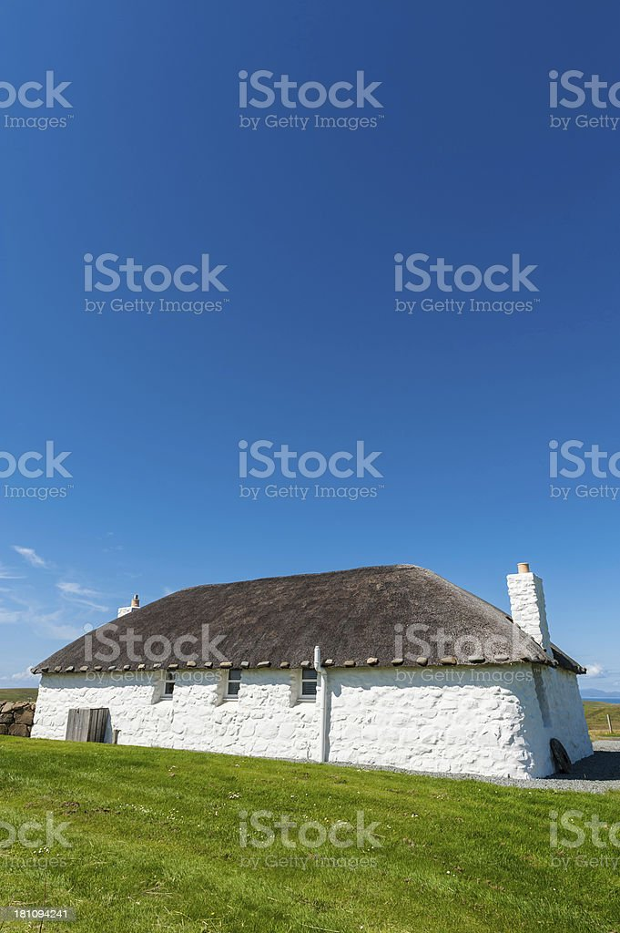 Quaint thatched cottage below clear blue summer skies stock photo