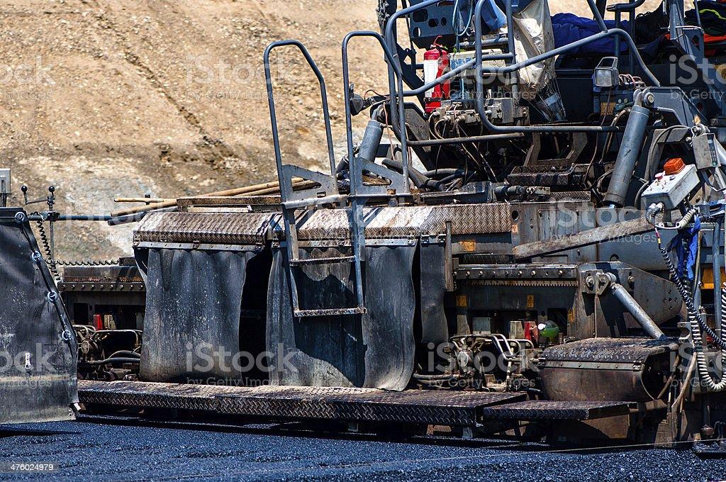 Qualified engineer operating asphalt paver machine stock photo