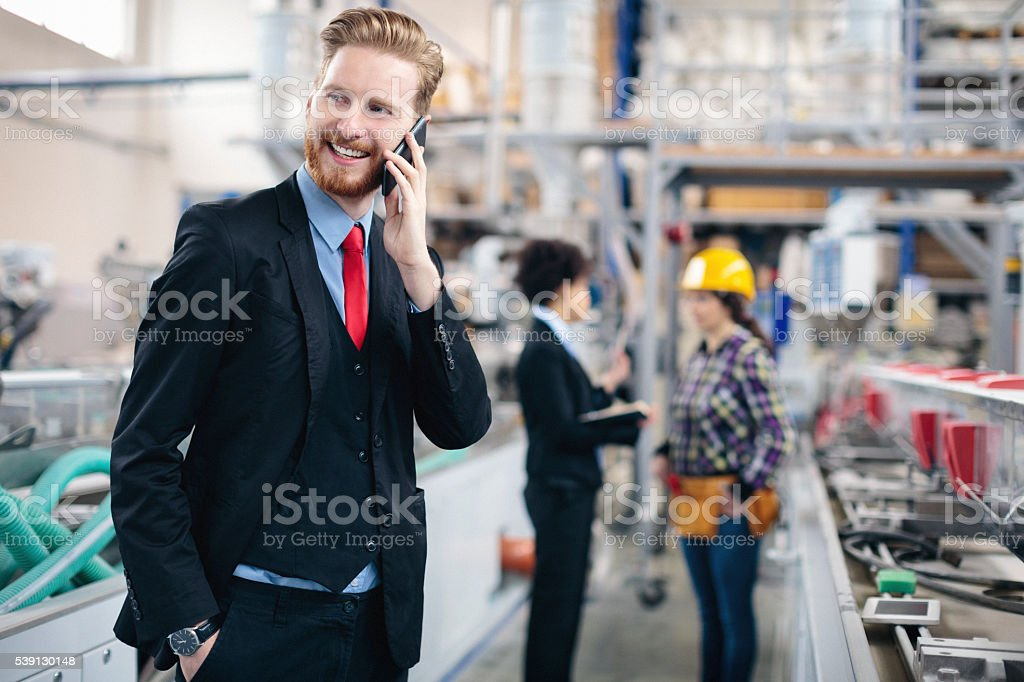 Quality inspector in a factory talking on the cell phone stock photo